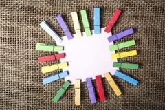Pinzas en blanco de la nota y del color fotos de archivo