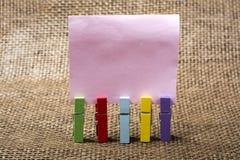 Pinzas en blanco de la nota y del color fotografía de archivo libre de regalías