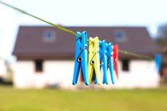Pinzas que cuelgan en un cordón delante de la casa Imagenes de archivo