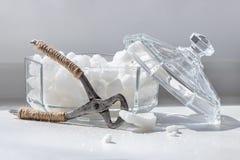 Pinzas viejas para el azúcar de terrón y el cuenco de azúcar del vidrio que parten con l fotos de archivo