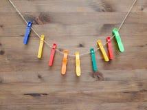 Pinzas y cuerda coloreadas en el fondo de madera Fotos de archivo libres de regalías