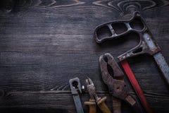 Pinze arrugginite delle pinze del seghetto a mano per metalli sul concep della costruzione del bordo di legno Fotografia Stock Libera da Diritti