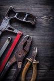 Pinze d'annata arrugginite del tagliafili della sega a mano sul constru del bordo di legno Immagini Stock Libere da Diritti