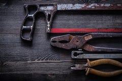 Pinze d'annata arrugginite delle pinze della sega a mano su di legno Fotografie Stock