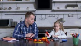 Pinze del papà di rappresentazione della ragazza durante la lezione domestica del mestiere archivi video