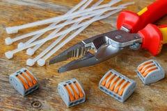 Pinze di combinazione per il cablaggio con la tirata di plastica bianca ed il terminale filo a scatto rapido sulla tavola di legn immagini stock libere da diritti