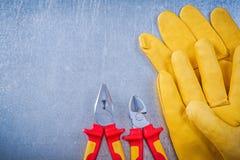Pinze di cuoio delle pinze dei guanti di sicurezza su fondo metallico elett. Immagini Stock Libere da Diritti
