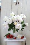 Pioenen en aardbeien Boeket van pioenen in een witte waterkruik Stock Afbeeldingen