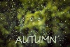 Pioggia di autunno, l'iscrizione sul vetro bagnato - autunno Smiley triste delle gocce di pioggia immagini stock