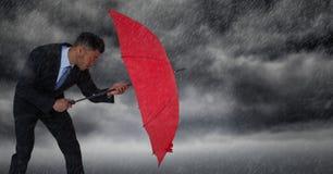 Pioggia di didascalia dell'uomo di affari con l'ombrello contro le nuvole di tempesta Fotografie Stock