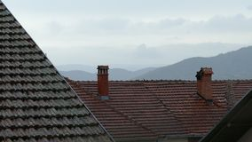 Pioggia di estate che cade sui tetti e sui camini di mattonelle rosse stock footage