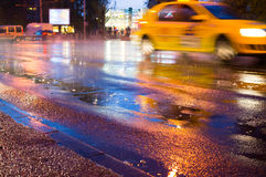 Pioggia di notte nella città con le gocce di pioggia ed il taxi immagini stock