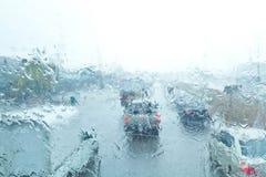 Pioggia di traffico (messa a fuoco sulle gocce di pioggia su vetro) Immagine Stock
