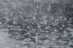 Pioggia persistente che si schianta sulla pavimentazione di strada fotografia stock