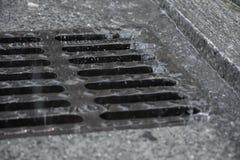 Pioggia persistente che si schianta sulla pavimentazione di strada e nella botola fotografia stock libera da diritti