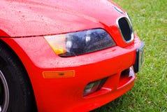 Pioggia su un'automobile rossa immagine stock