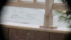 Pioggia sul balcone che trascura il mare stock footage