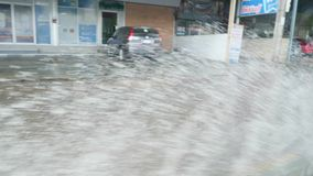 Pioggie persistenti nell'inondazione di Bangkok, Tailandia Pozze dell'acqua profonda di guida di veicoli in città Clima che cambi stock footage