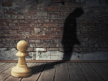 The pawn feeling. A white pawn piece into a dark room with its man silhouette shadow on a brick wall Stock Images