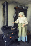 Pioneer Cook. A pioneer woman cooking bratwurst on an old fashioned cast iron stove at Old World, Wisconsin in Eagle, WI royalty free stock images