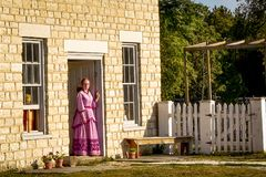 Pioneer Lady in Doorway. A pioneer woman interpreter from Old World Wisconsin, in a pink dress, stands in the doorway of the Country Store located on the grounds Royalty Free Stock Image