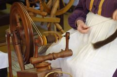 Vintage wooden spinning wheel in use stock images