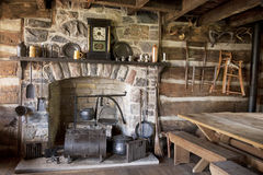 Pioneer Living Room. The fireplace and utensils of an old pioneer log home royalty free stock image