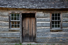 Log Cabin. A closeup of a weathered century log home sagging in the middle Stock Image