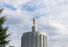 Pioneer Stands Alone. The gold pioneer that stands on Oregon's Capitol Building in Salem enjoys a rare sunny winter day stock images