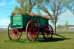 Pioneer Wagon. A restored red and green pioneer wagon sits at rest with hay loaded Royalty Free Stock Photography