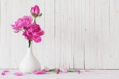 Pionen blommar i vas Arkivfoto