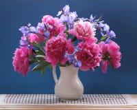 Pioner och iriers Den härliga buketten av trädgården blommar i en tillbringare royaltyfri bild