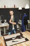 Pionowo portret skoncentrowany caucasian męski projektant pracuje na nowej kolekci, trzymający rękę na podbródku, patrzeje Obraz Royalty Free