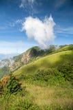 Pionowo scena zielona góra z niebieskim niebem i chmurą Fotografia Stock
