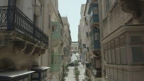 Pionowo spadek, trutnia latanie przez pięknej starej ulicy, Valletta, Malta Stary, roczników okno, balkony - 4K zbiory