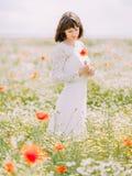 Pionowo widok panny młodej mienie, patrzeć maczka w wiosny polu i Zdjęcia Royalty Free