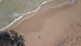 Pionowo widok z lotu ptaka dziewczyny lying on the beach w opustoszałej plaży zbiory