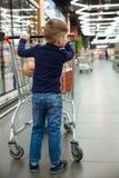 Pionowo wizerunek młoda chłopiec z zakupy tramwajem Zdjęcie Stock