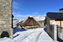 Piornedo, Ancares, Galicia, Spain. Ancient snowy palloza house made with stone and straw. Mountain village, winter and snow. royalty free stock photography