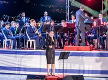 Piosenkarz, towarzyszący mosiężnym zespołem, wykonuje piosenkę przy pamiątkową ceremonią w Pamiątkowym miejscu Spadać w Izrael obraz royalty free