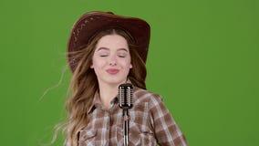 Piosenkarz w wizerunku kowboj śpiewa w retro mikrofonie zielony ekran zdjęcie wideo