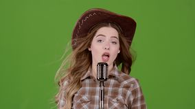 Piosenkarz w wizerunku kowboj śpiewa w retro mikrofonie zielony ekran swobodny ruch zbiory