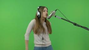 Piosenkarz z długie włosy śpiewa w pracownianego mikrofon Na zielonym tle zbiory