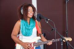 Piosenkarz Z oczami Zamykającymi Bawić się gitarę W studiu Obrazy Royalty Free