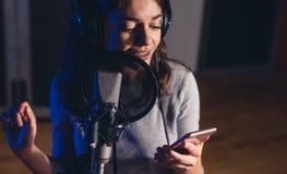 Piosenkarza śpiew w studiu nagrań z telefonem komórkowym Obraz Stock