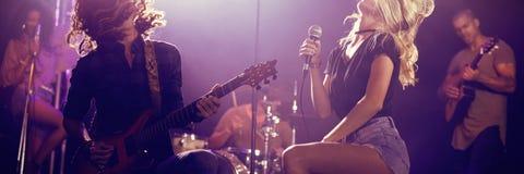 Piosenkarza i samiec gitarzysta z kudłacącym włosianym spełnianiem przy klubem nocnym Zdjęcia Royalty Free