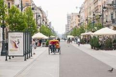 Piotrkowska街道在罗兹市的心脏 轮转人力车的人们 免版税库存图片