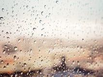 Piova in città, le gocce di acqua sul vetro di finestra bagnato, il tramonto Immagine Stock Libera da Diritti