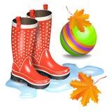 Piova i gumboots rossi con i punti in pozza, palla del giocattolo dei bambini verdi Fotografia Stock