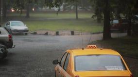Piova il versamento sulle automobili e su un taxi nella via con il suono Tuono e un fulmine video d archivio